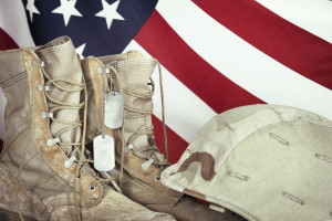 American Soldier combat boots, dog tags, and helmet with American flag